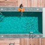 Jeune femme qui se prélasse au bord de sa piscine enterrée