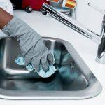 Femme qui nettoie un évier en inox avec un chiffon et des gants