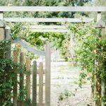 Portail blanc en bois et buissons qui délimitent un jardin