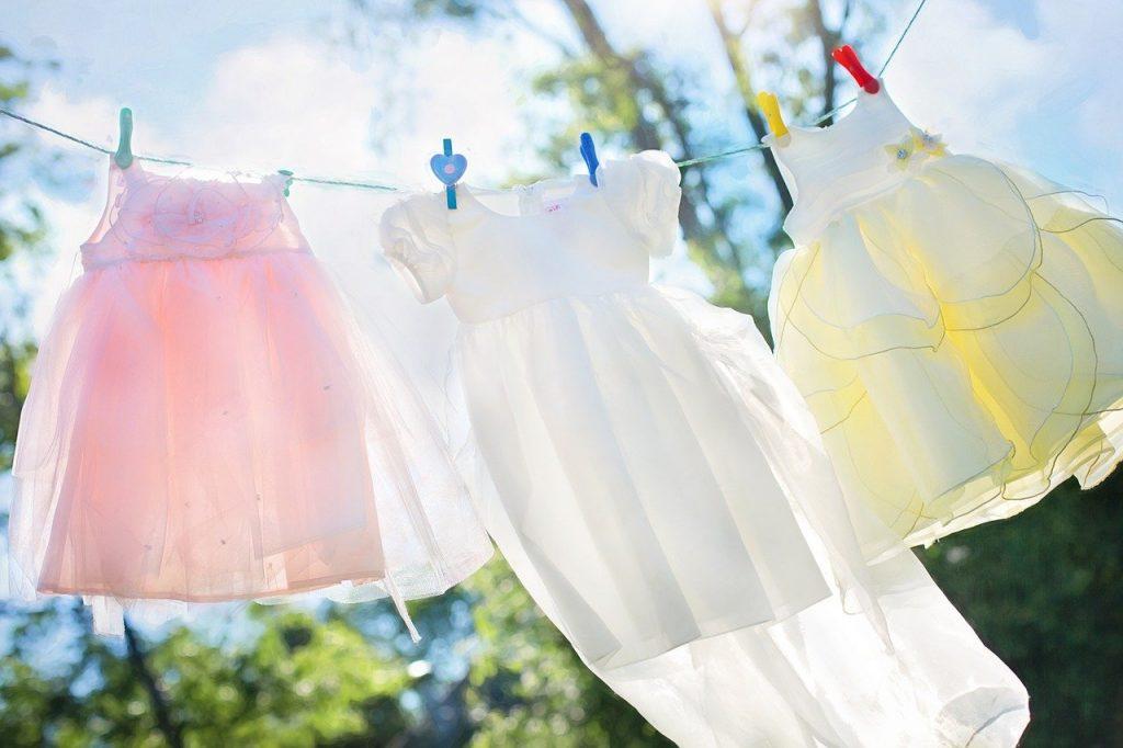 trois robes d'enfant qui sèchent à l'extérieur